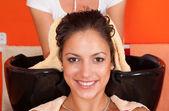 Beautiful young girl enjoying hair washing in hairdressing salon — Stock Photo