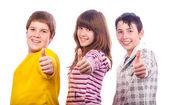 Two teenage boys and one teenage girl showing thumbs up — Stock Photo