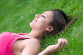 Beautiful happy girl lying on the green grass on warm summer day — Stock Photo