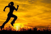 Silhouette of the running girl at sunrise — Stock Photo