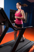 Beautiful smiling girl running on treadmill in the gym. — Stock Photo