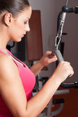 Beautiful young woman exercising arms in health club. — Stock Photo