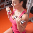 Beautiful smiling young woman exercising with dumbbells in the gym - Stock Photo