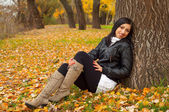 Beautiful smiling girl sitting on the bed of leaves in the autumn forest — Stock Photo