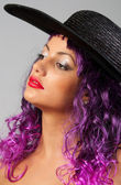 Portrait of beautiful sexy girl with purple hair and black hat — Stock Photo