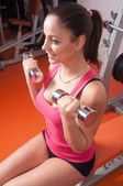 Beautiful smiling young woman exercising with dumbbells in the gym — Foto Stock