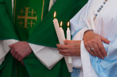 Detail of the advent mass showing robes and hands of priests holding three white candles — Stock Photo