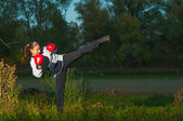 Beautiful kickboxing girl exercising high kick in the nature at night — Stock Photo