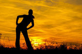 Silhouette of the slim girl stretching out in the nature at sunrise — Stock Photo