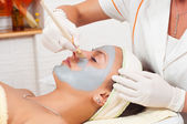 Beautiful young woman lying on massage table while facial mask is put on her face — Stock Photo