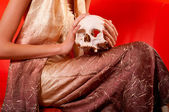 Elegant lady holding human skull while sitting on red sofa — Stock Photo