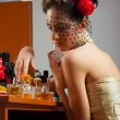 Beautiful old fashioned lady plays with perfumes in front of the mirror — Stock Photo