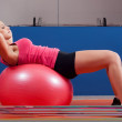 Beautiful young girl exercising abdomen muscles in the gym while lying on big rubber ball — Stock Photo #17890929