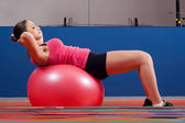 Beautiful young girl exercising abdomen muscles in the gym while lying on big rubber ball — Stock Photo