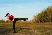 Beautiful kick boxing girl exercising kick in the nature on sunny summer day — Stock Photo