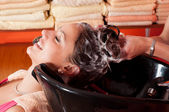 Beautiful young girl enjoying hair washing in hairdressing salon — Stock Photo
