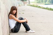 Cute sad teenage girl sitting alone in urban environment — Stok fotoğraf