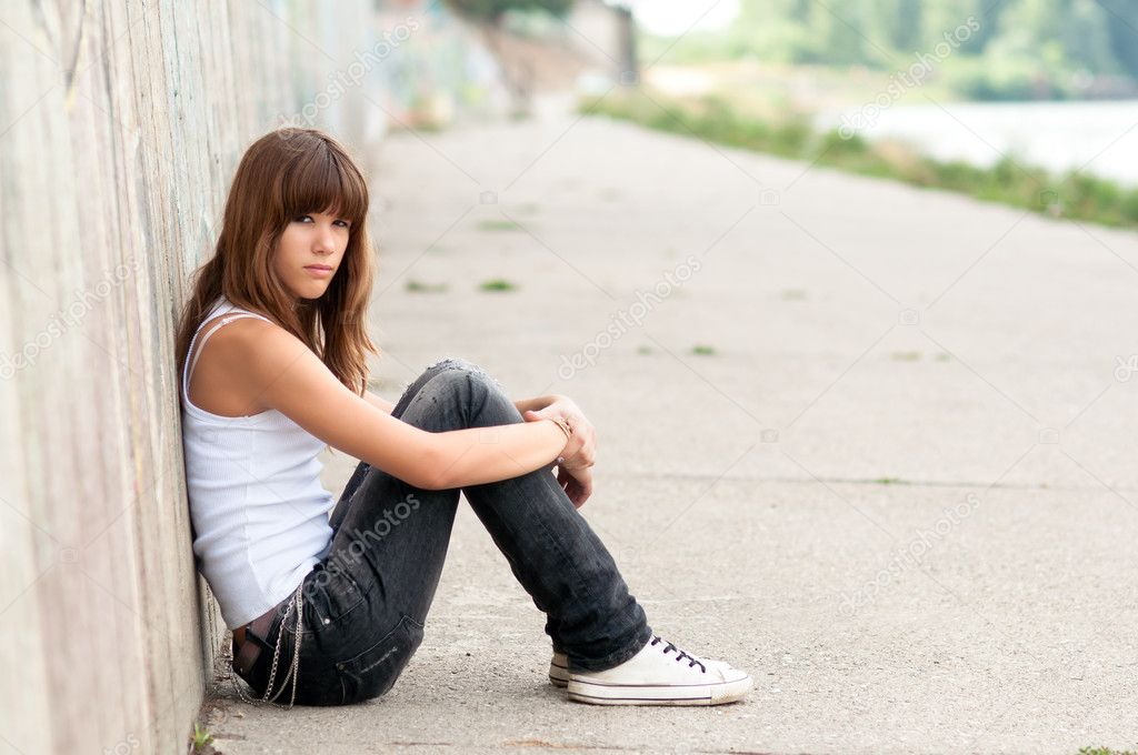 Cute sad teenage girl sitting alone in urban environment ...