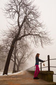 Lonely teenage girl watching the mist on cold winter day — Stock Photo