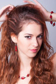Portrait of the beautiful fashionable girl with long red hair and red jewelry — Stock Photo