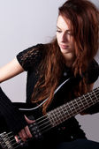 Beautiful girl in black plays black bass guitar — Stock Photo