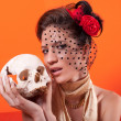 Beautiful elegant lady holding human skull — Stock Photo