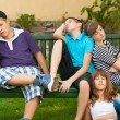 Stock Photo: Teenage boys and girls resting on bench on beautiful summer day