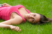 Beautiful smiling girl lying on the grass on calm spring day — Stock Photo