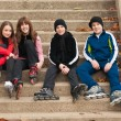 Group of happy teenagers in roller skates sitting on the stairs on beautiful autumn day — Stock Photo