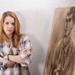 Young female artist posing beside her artwork. — Stock Photo