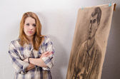 Young female artist posing beside her artwork. — Stock Photo