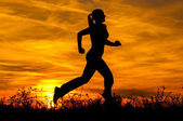 Silhouette of the running girl at sunrise. — Stock Photo