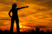 Silhouette of the young woman pointing to something in the distance at sunrise. — Stock Photo