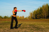 Beautiful kick boxing girl exercising in the nature on sunny summer day. — Stock Photo