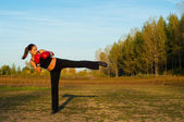 Beautiful kick boxing girl exercising kick in the nature on sunny summer day. — Stock Photo