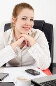 Retrato de uma bela mulher de negócios sorridente, sentado em seu escritório — Fotografia Stock