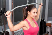 Beautiful smiling young woman exercising with weights in the gym — Stock Photo