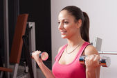 Beautiful smiling young woman exercising with dumbbells in the gym — Stock Photo