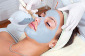 Beautiful young woman lying on massage table while facial mask is put on her face. — Stock Photo