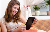 Cute teenage girl reading novels on ebook reader while sitting on the couch — Stock Photo