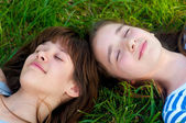 Happy teenage girls lying in the grass on beautiful spring day — Stok fotoğraf