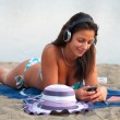 Beautiful sexy girl lying on the sandy beach at summer and listens to music — Stock Photo #21757863