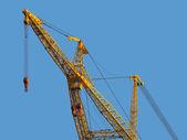 Huge construction crane against clear blue sky. — Stock Photo