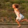 Royalty-Free Stock Photo: Cute little girl in white dress running on sunny spring day