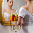Beautiful bride in wedding dress looking at herself in the mirror — Stock Photo #23307058