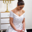 Beautiful bride in wedding dress kneeling on the floor and looking at her wedding ring — Stock Photo #23332830