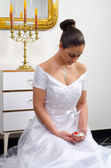 Beautiful bride in wedding dress kneeling on the floor and looking at her wedding ring — Stock Photo