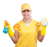 Happy cleaning lady in uniform wearing gloves, cap and holding detergent and sponge — Stock Photo