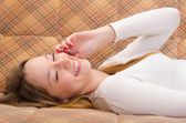 Beautiful happy teenage girl talking on the mobile phone while lying on the bed — Stock Photo