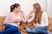 Two teenage girlfriends trying out perfumes — Stock Photo